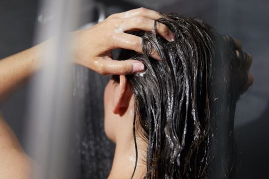person putting shampoo in hair