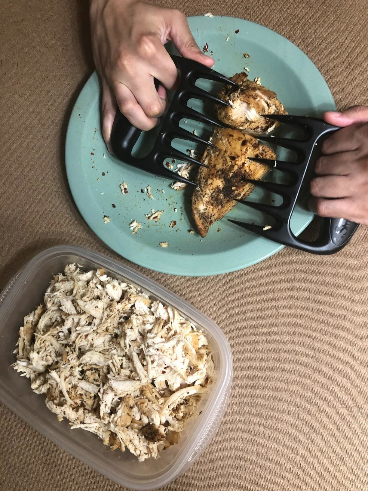 A reviewer's hands using the claws the shred some chicken