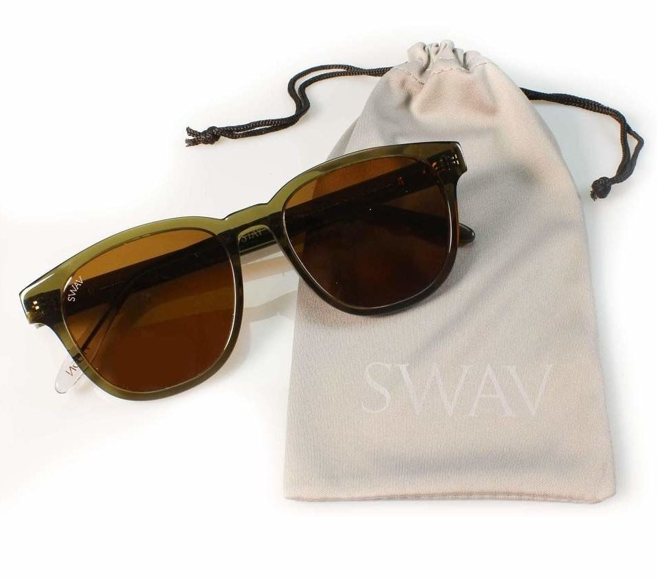 """The oval sunglasses with olive green frames and brown lenses on top of a bag with the word """"Swav"""" on it"""