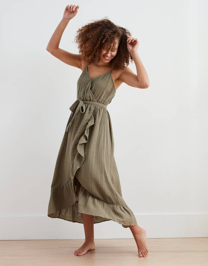 model in olive green wrap midi dress with belt tie, spaghetti straps, and ruffle down the front and along bottom edge