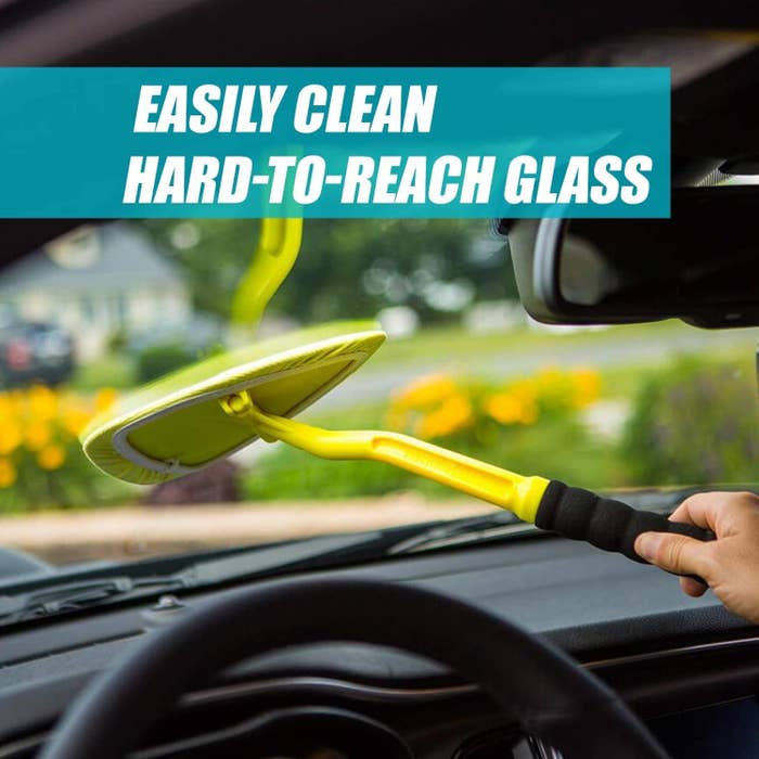 Hand using the tool, which looks like a giant guitar pick wrapped in a microfiber cloth and attached to a stick, to wipe the inside of a windshield
