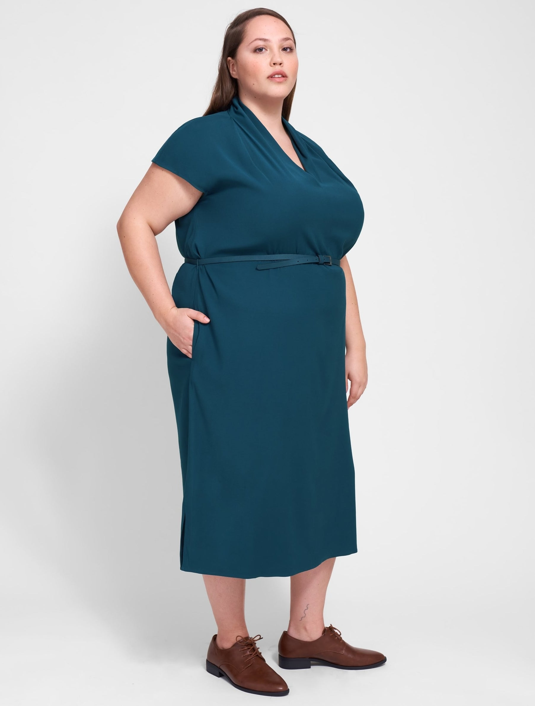 model in teal dress with short sleeves, V-neck, and high ruched collar