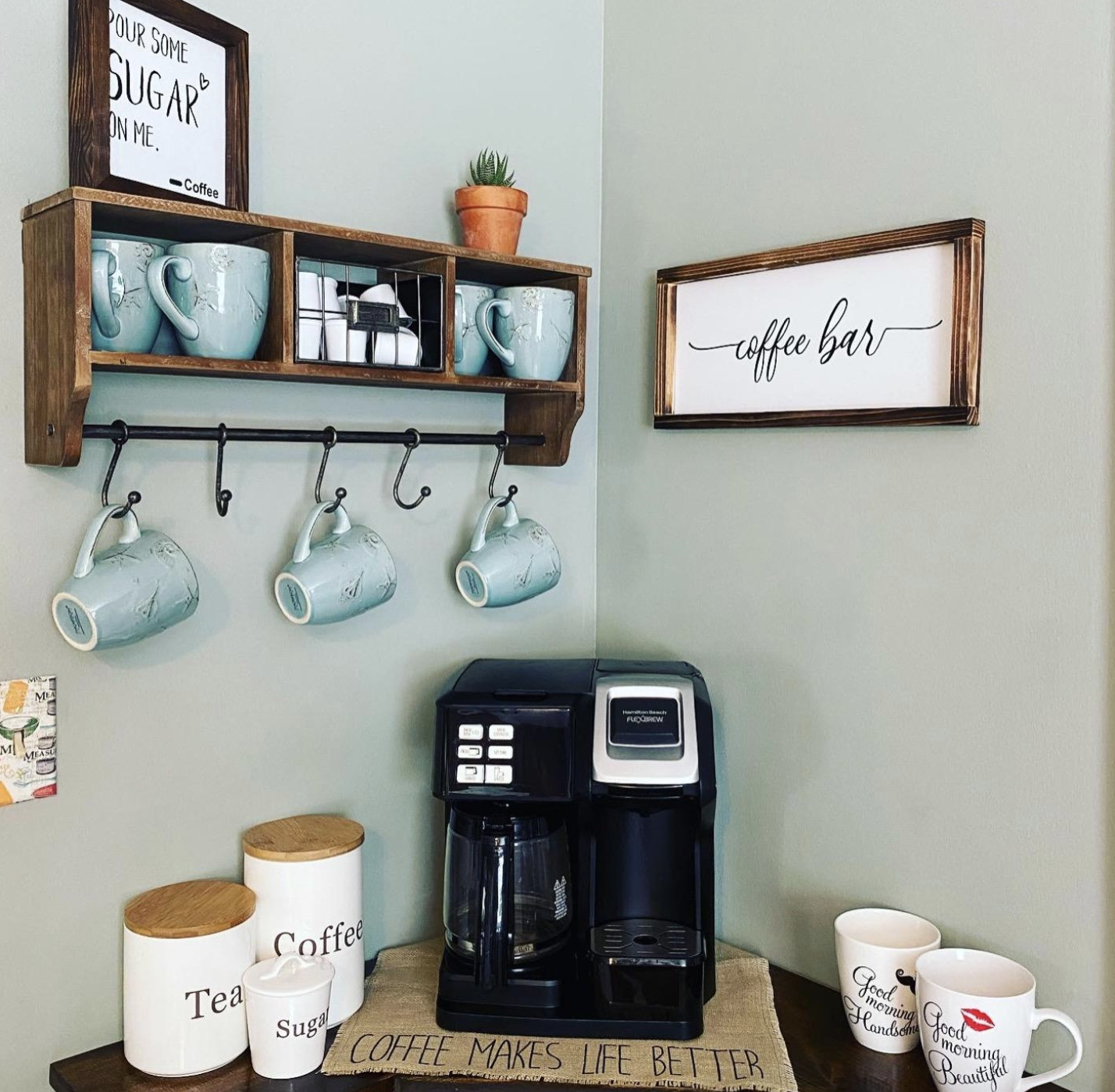 Reviewer image wooden shelf with three compartments holding mugs and K-cups, plus a bar with hooks for additional mug storage