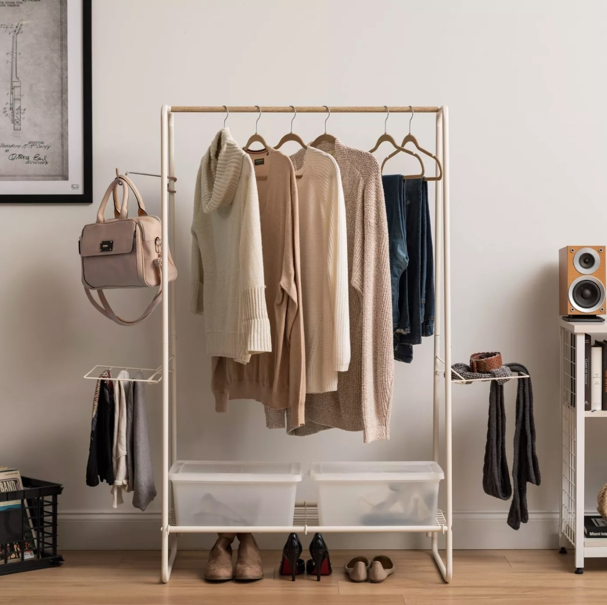 A thin white garment rack with a bottom shelf