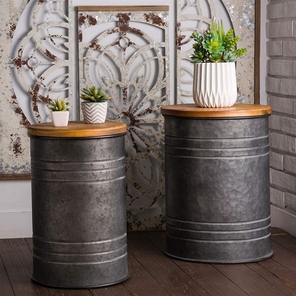 Two metal stools with a vintage milk canister vibe, each artistically worn with dents and discoloration. The lids have a smooth, natural wood finish.