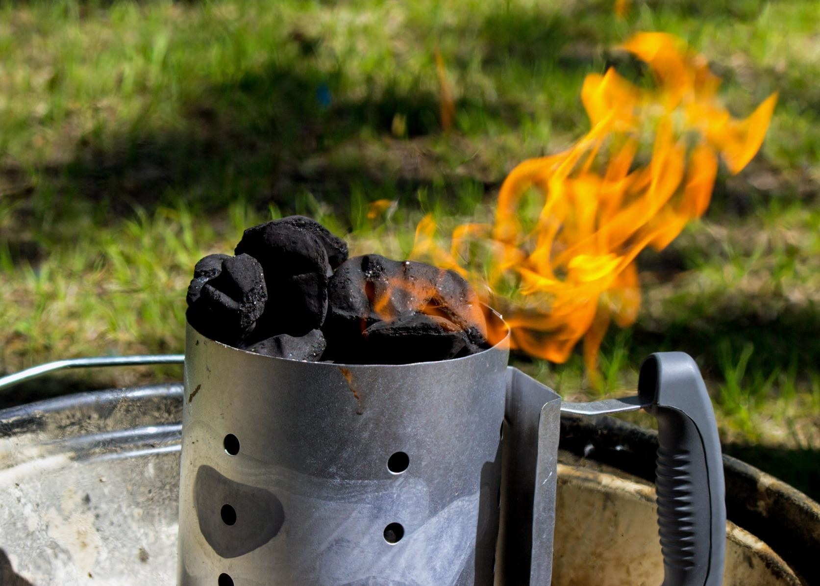 A reviewer's photo of the chimney starter in use with flames shooting from the charcoal