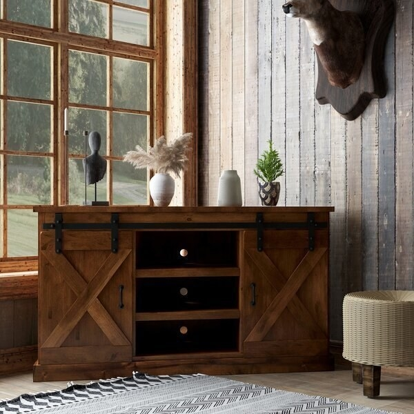 A large corner table with hardware and wood sliding barn door details. It has three shelves, two doors, and a large surface area on the top.