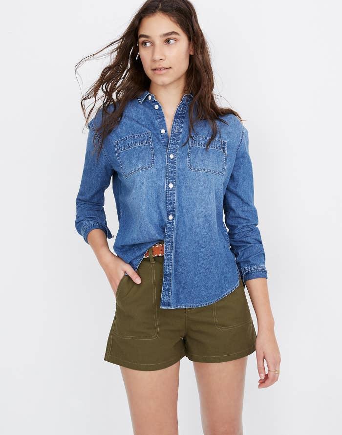 Model wearing button-down blue chambray shirt
