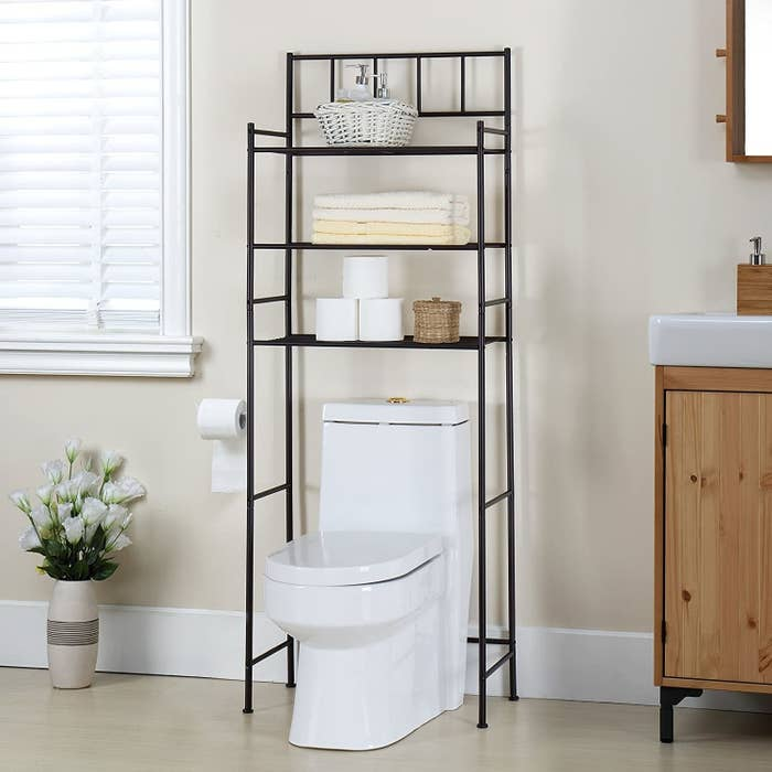 A minimalist shelving unit made of thin black pipes. It has three shelves that are high enough to go above the toilet tank.