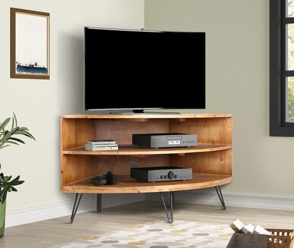 A two shelf console with hairpin legs placed snug into a corner of a room. It has a TV on the table top.