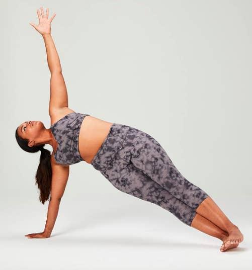 Model wears black tie-dye printed crop leggings while completing a yoga pose