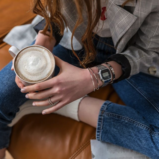 A person wearing the watch holding a cup of coffee