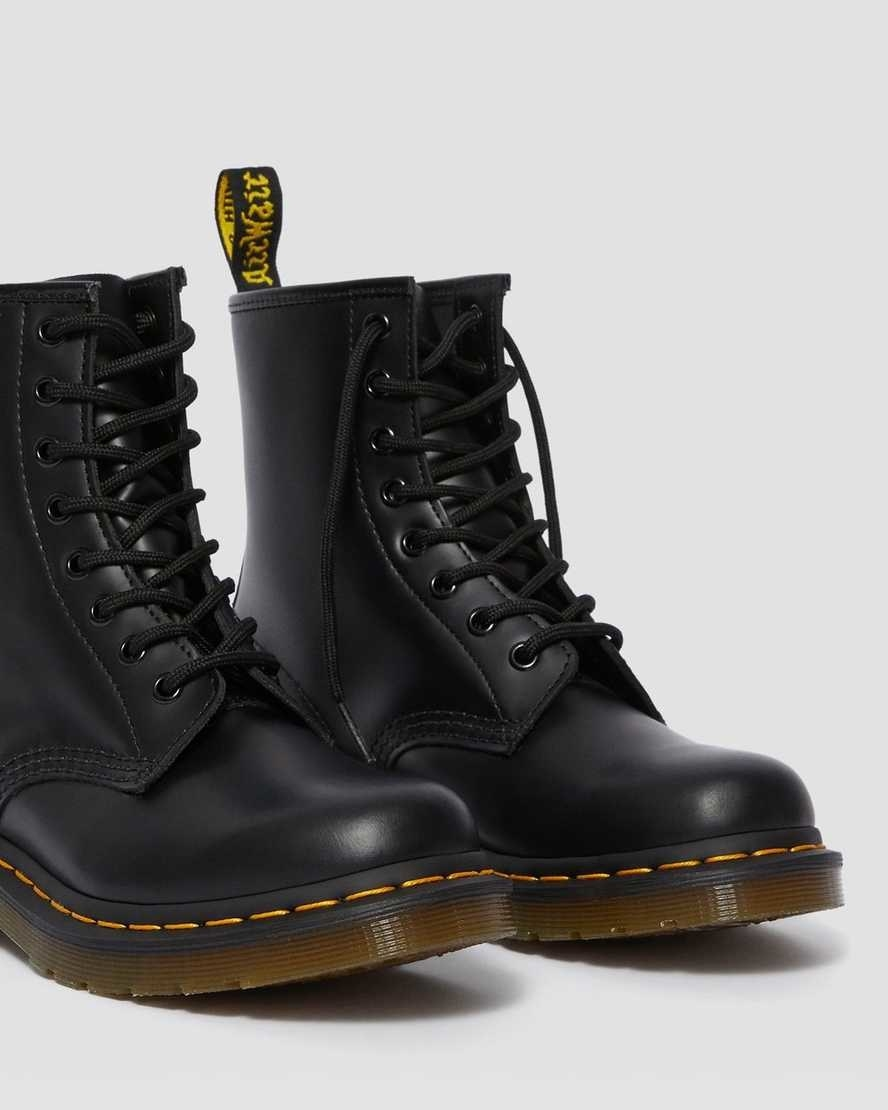 The boots with thick brown soles and yellow stitching around and a black ankle-length with black ties