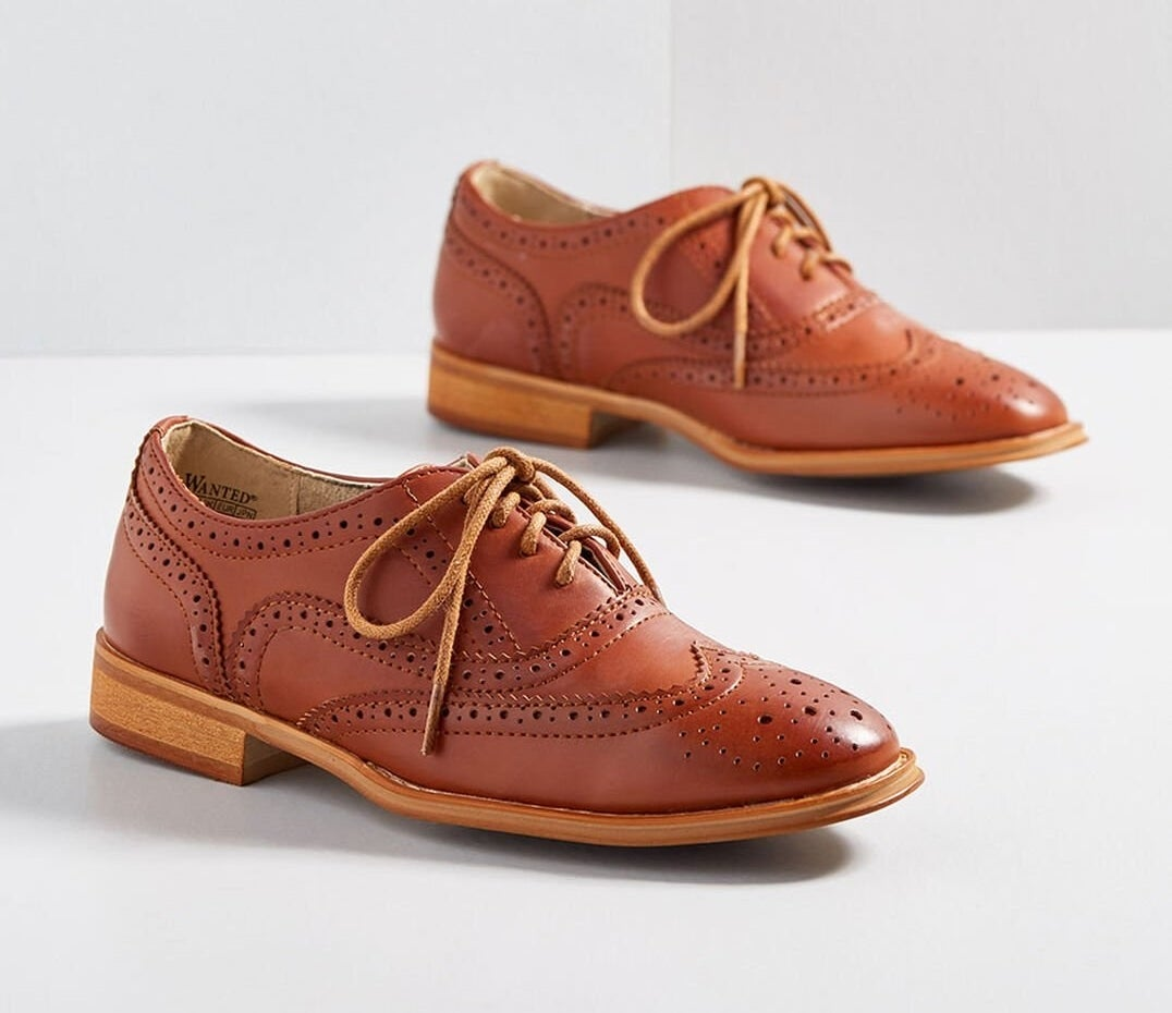 The oxford shoes in brown with a one-inch heel, laces, and perforated pattern throughout