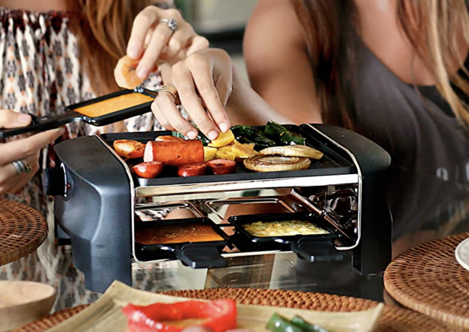 People eating from the four person raclette with a grill on top on a place to put your own grill on the bottom