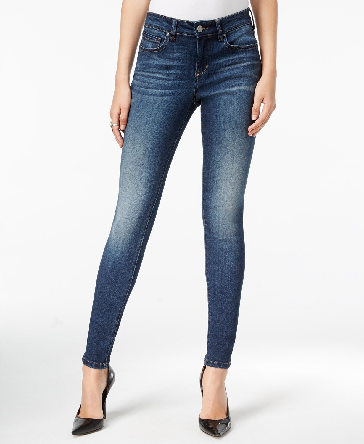 Model wearing the skinny jeans in blue with lighter coloring around the knees and whiskering near the waist