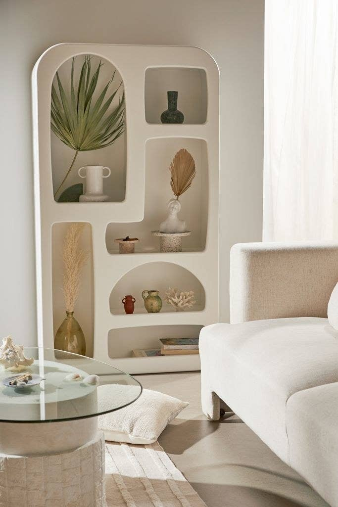 An abstract bookcase with shelves of different shapes and sizes, most with rounded edges. Some are vertical and some horizontal.