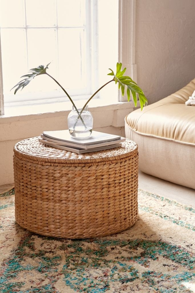 The ottoman is round with rattan braiding throughout and a removable lid on top