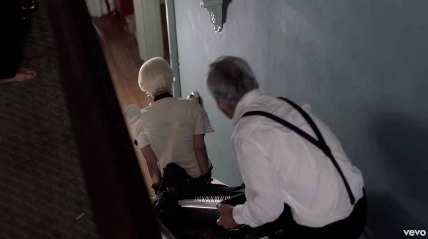Gaga carrying a piano downstairs with the help of a man with gray hair and suspenders