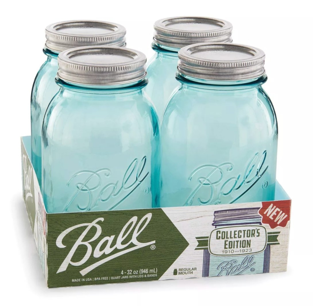 Four light blue glass jars with silver tops