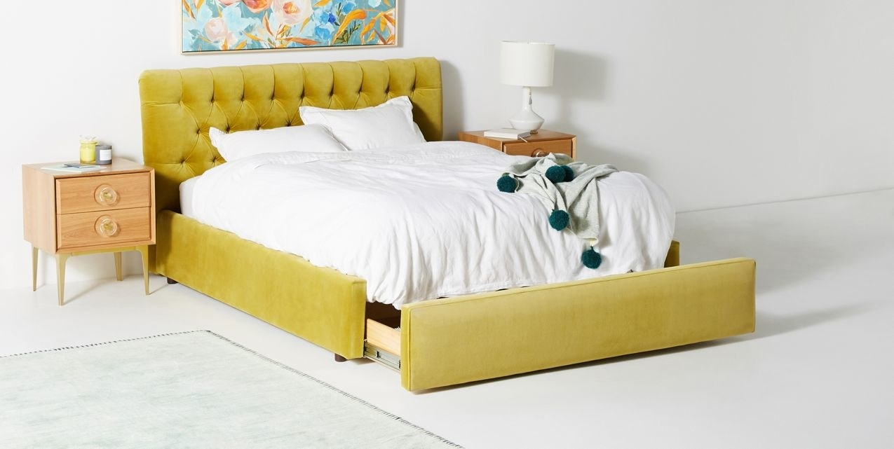 A full bed frame with a tufted headboard and a small storage space that can be pulled out from the foot of the bed. The edges of the frame match the velvet headboard.