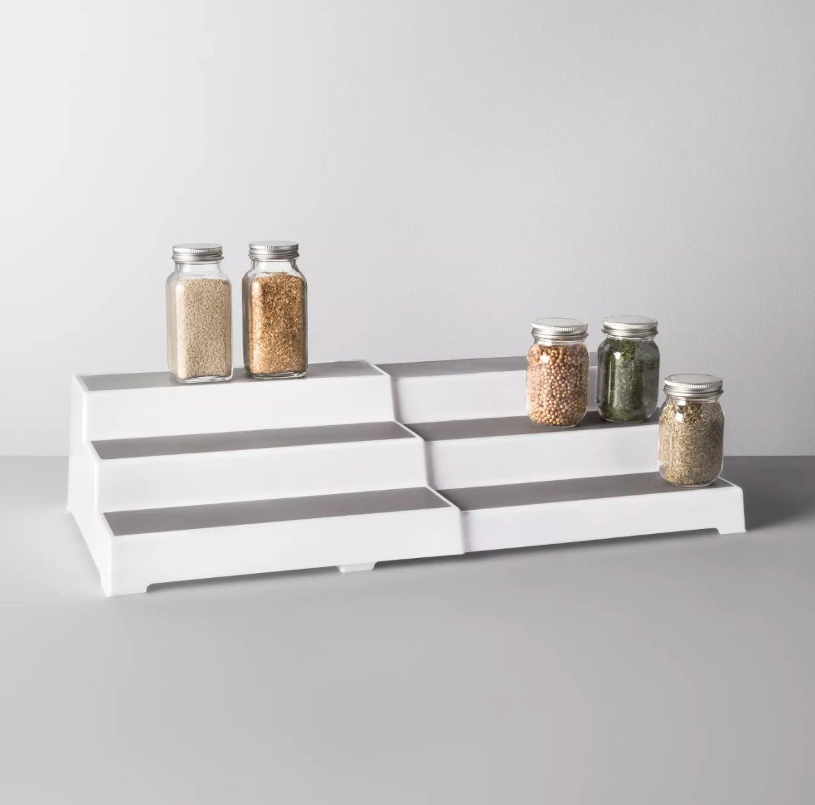A white riser that looks like three steps with gray tops holding jars