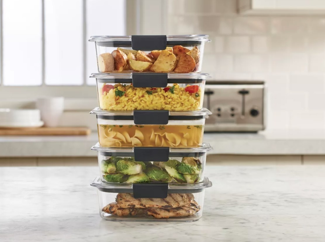 Five stacked food containers with gray snap lids filled with food