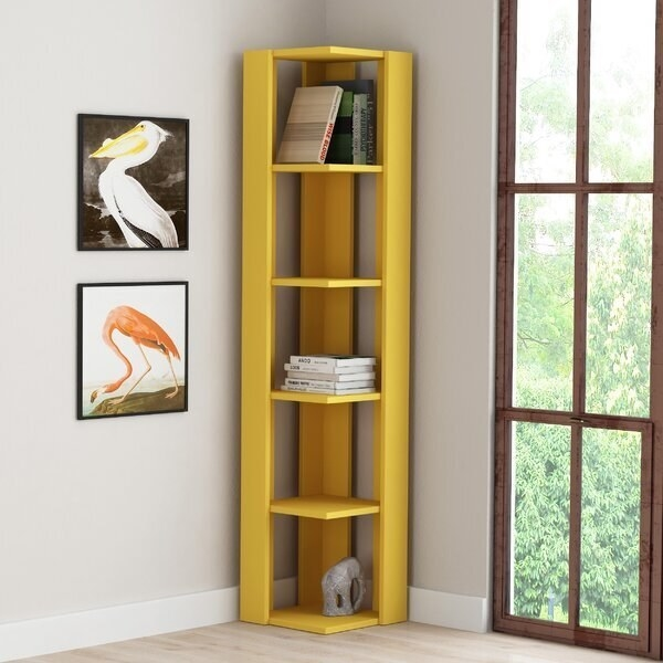 A tall, thin bookcase with five shelves fitting perfectly in the corner of a small room