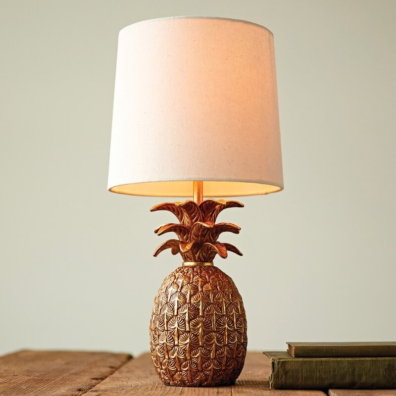 A lamp with a bronze-looking pineapple-shaped base and cylindrical shade