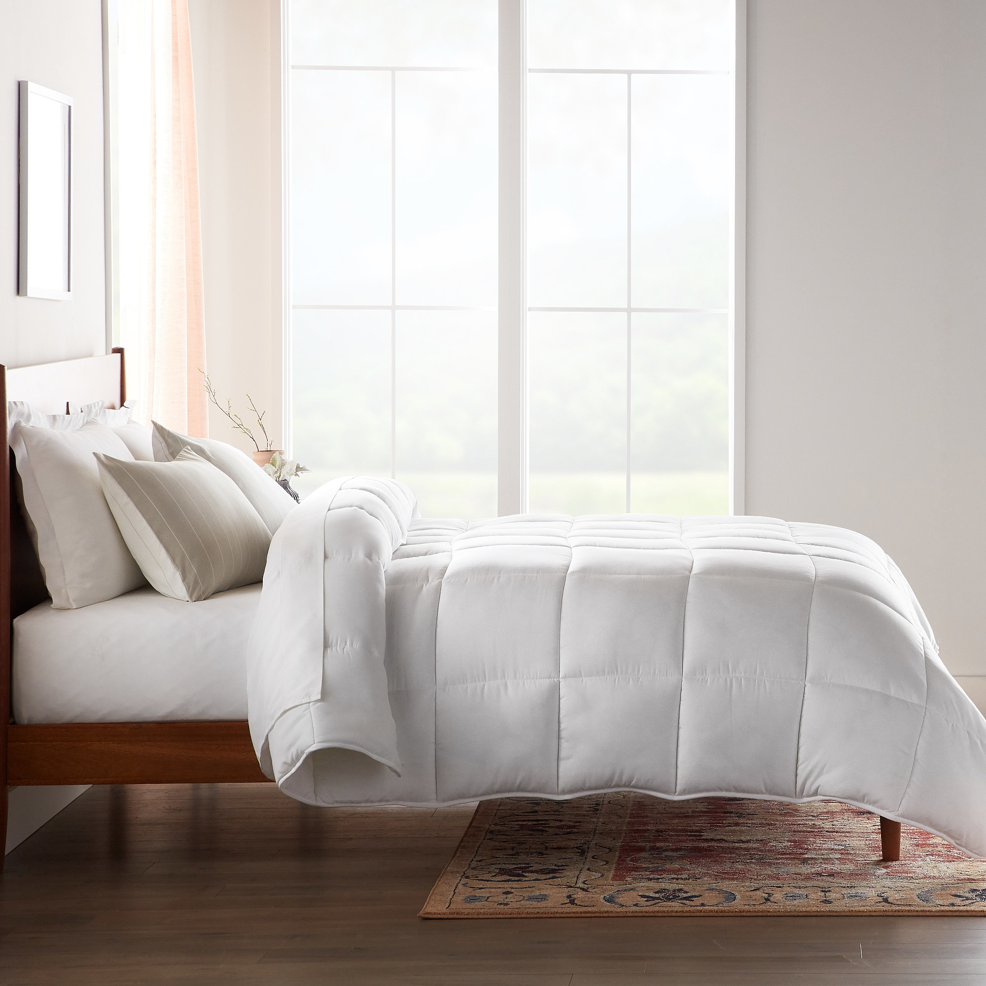 A quilted white comforter atop a bed