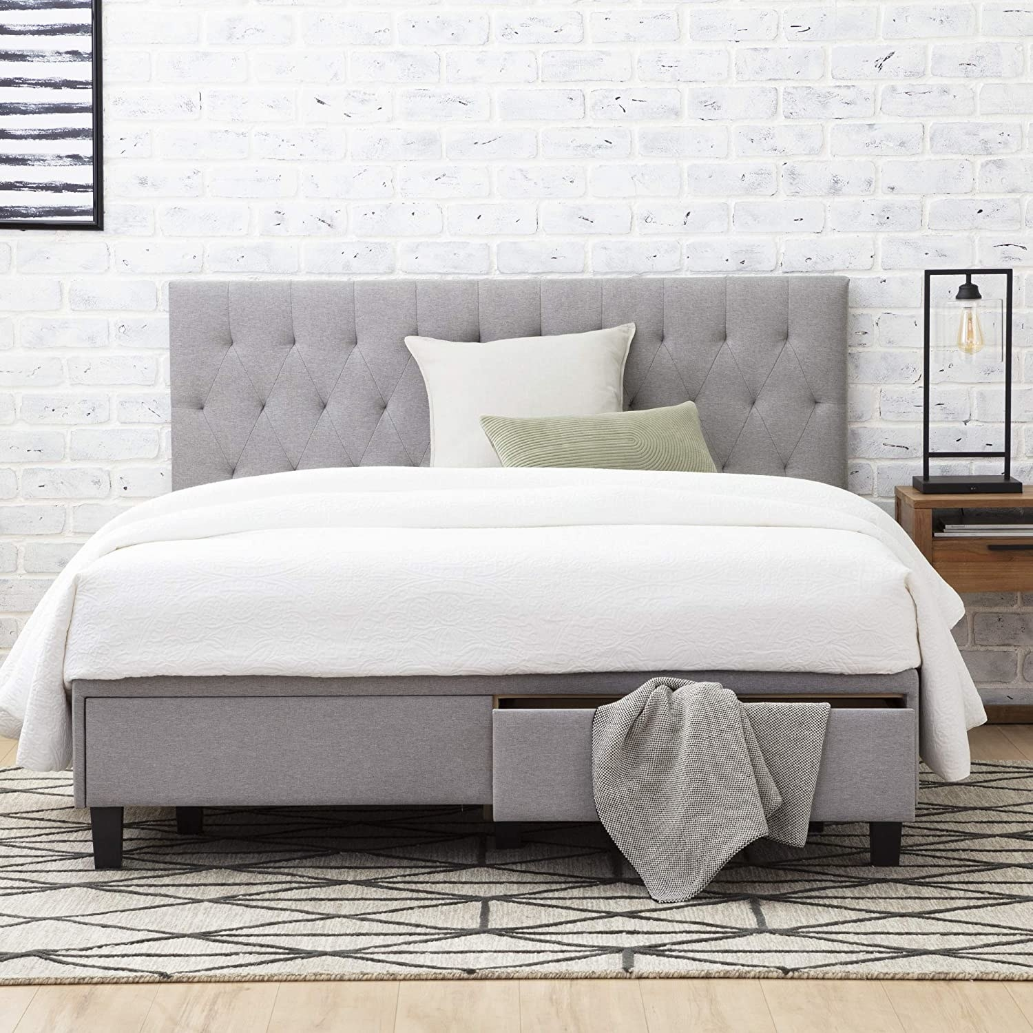 A simple gray fabric-covered frame with a tufted headboard, short feet, and two storage drawers at the foot of the bed