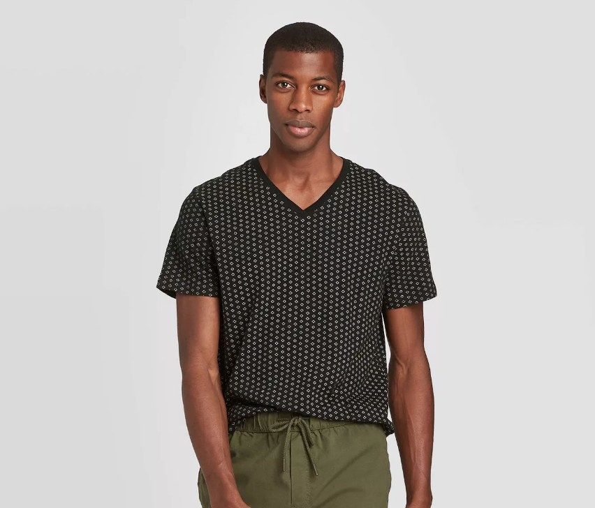 a model in a black v-neck tee with a pattern on it