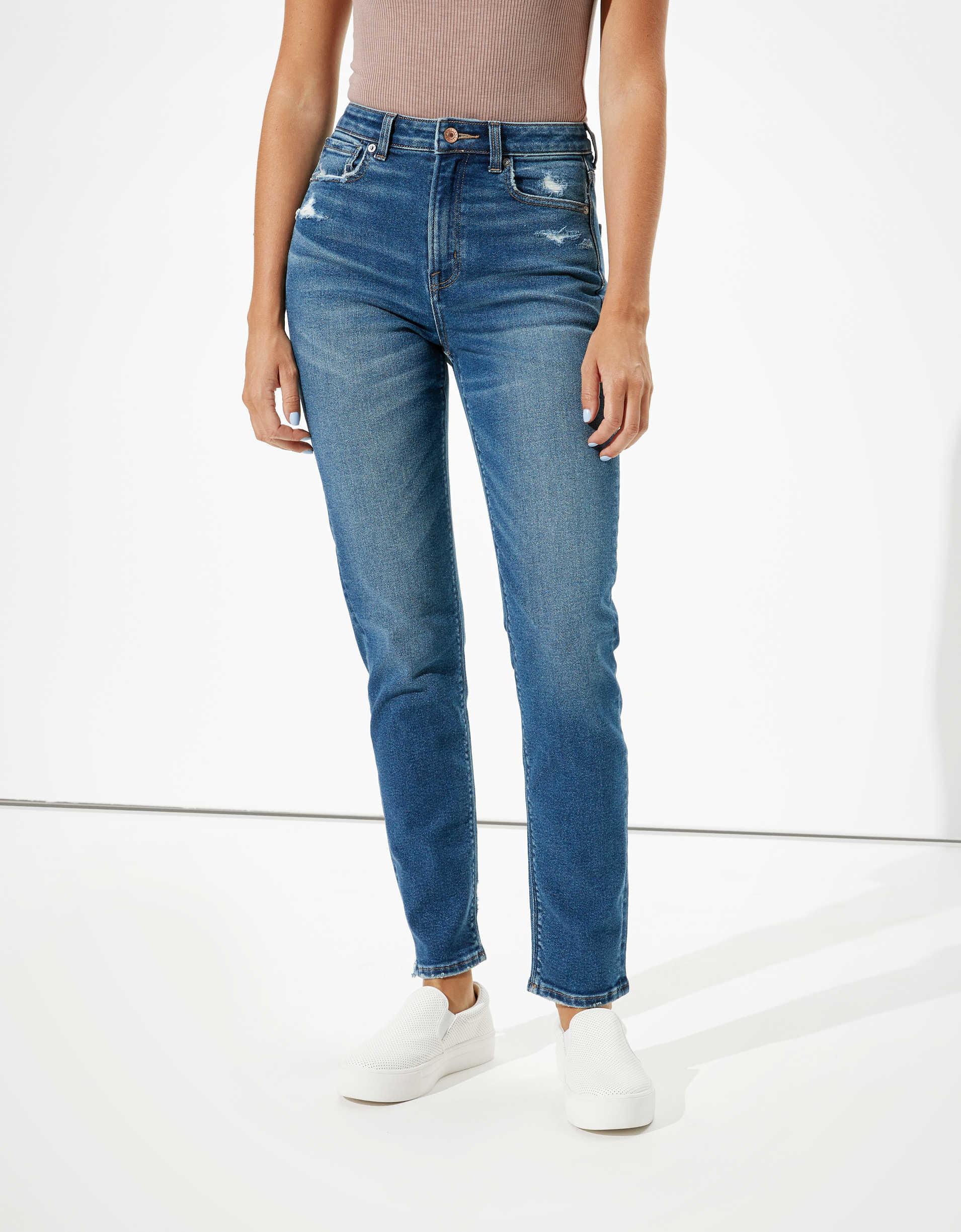 Model wearing the jeans in blue with a high waist and tapered leg