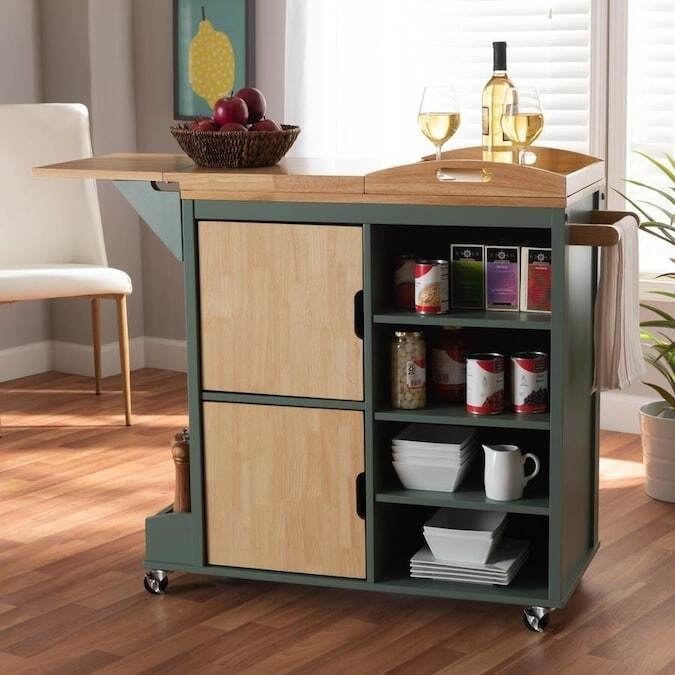 A moss green rolling kitchen kart with four exposed shelves, two larger shelves covered in natural wood, a removable tray table top and an adjustable counter top. It also has a shallow shelf for small bottles at the bottom and a hanger for dish towels.