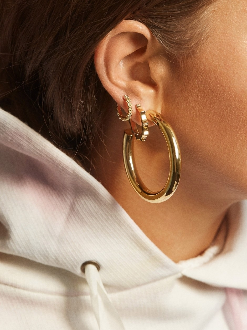 Model wearing the large gold hoops
