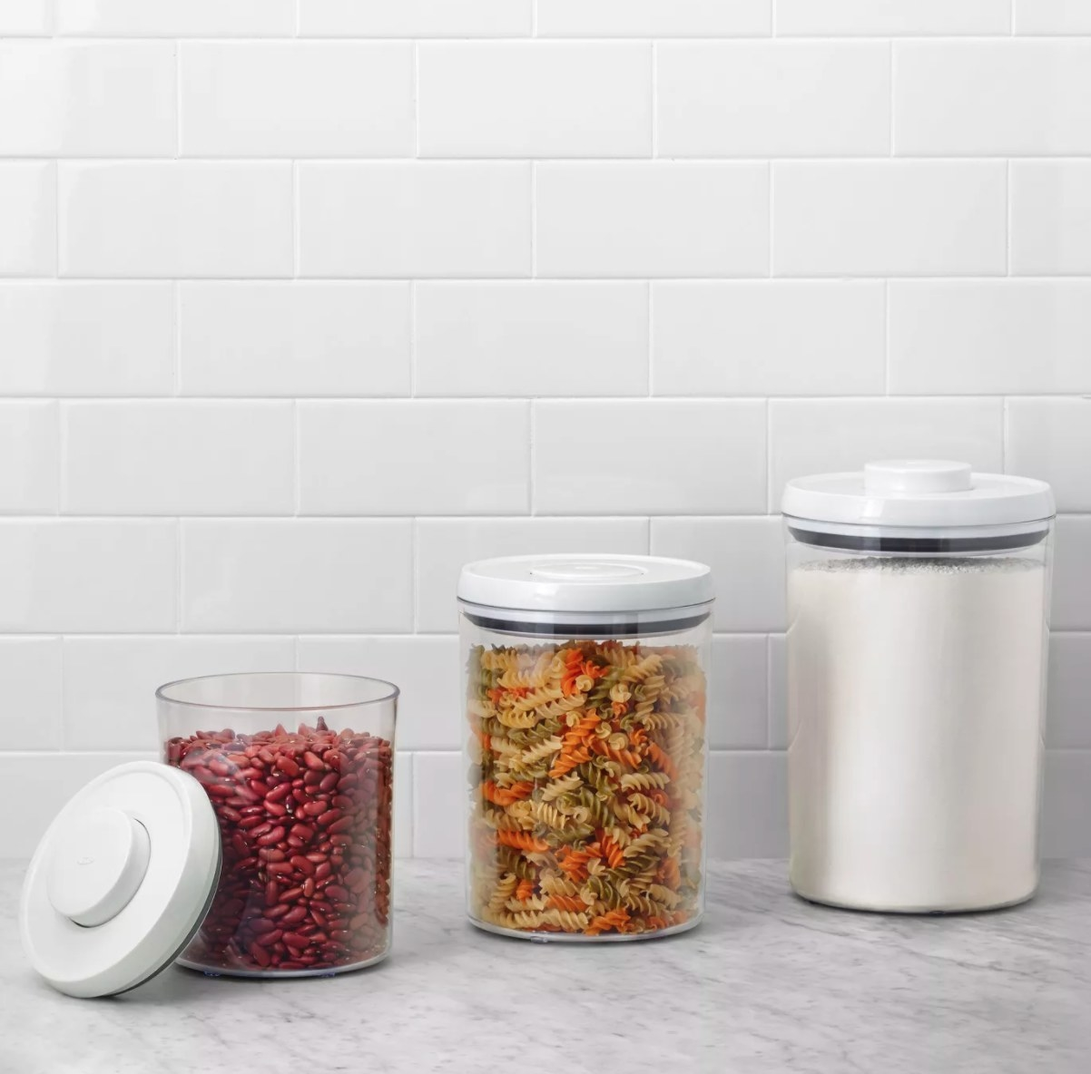 Three round plastic see-through canisters with white tops filled with foodstuffs
