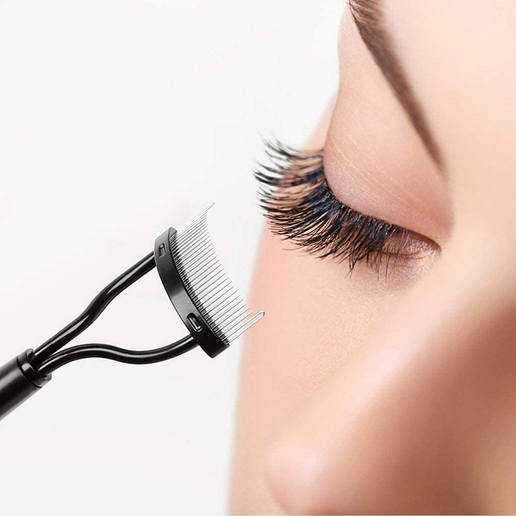 A close up of a person using the brush to comb out their eyelashes