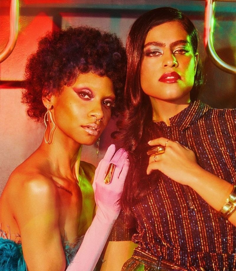 two models pose with large rectangular gold rings that cover bottom half of middle finger