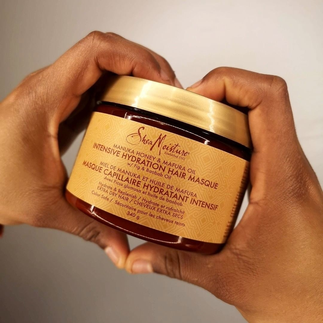 A person holding a tub of Shea Moisture hair masque