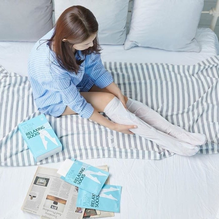 A person putting on the moisturizing socks on their bed