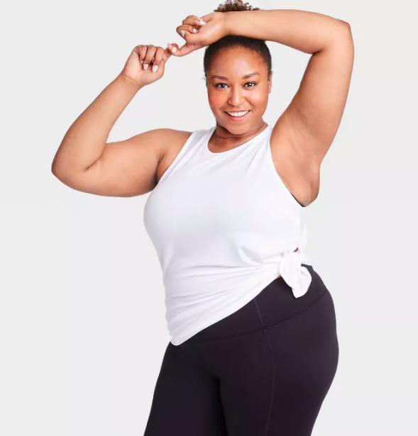 Model wears white side-tie top with black workout leggings