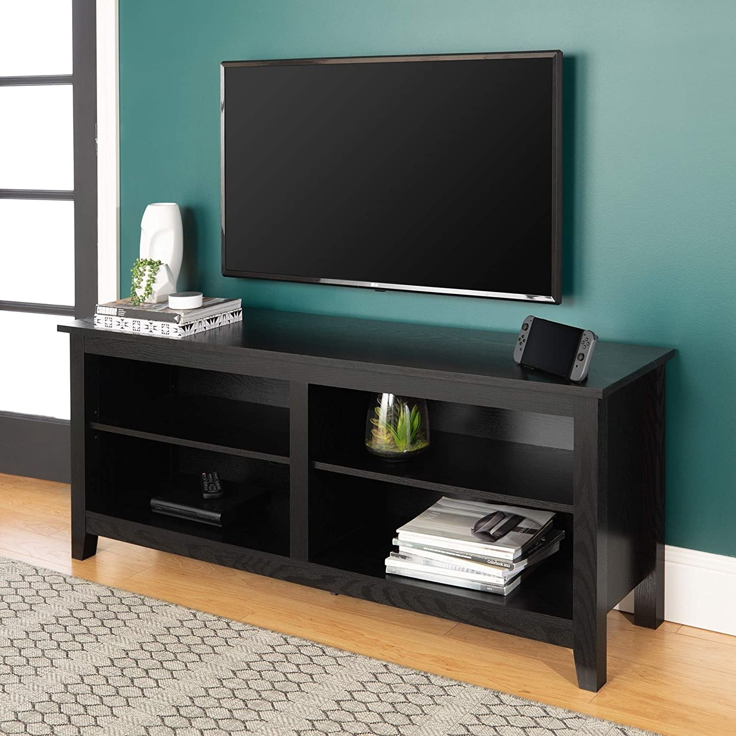 The storage console in black with four shelves filled with assorted things