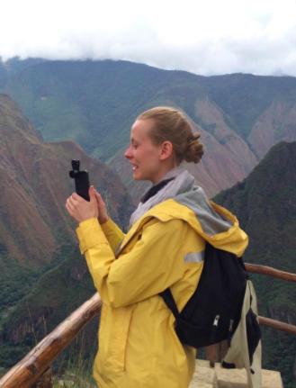 Reviewer wears yellow wind and waterproof rain jacket on a hike in Peru