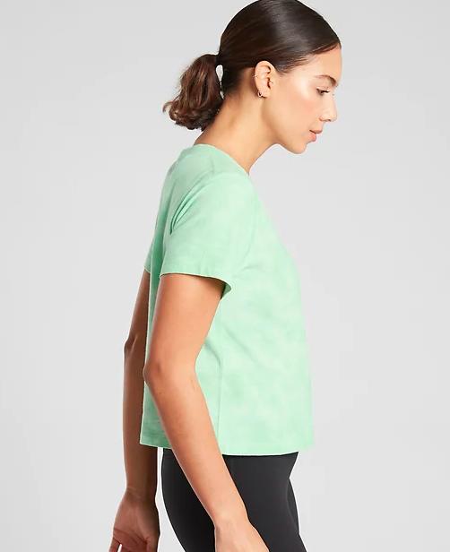 Model wears Athleta bright green tie-dye crop tee with black leggings