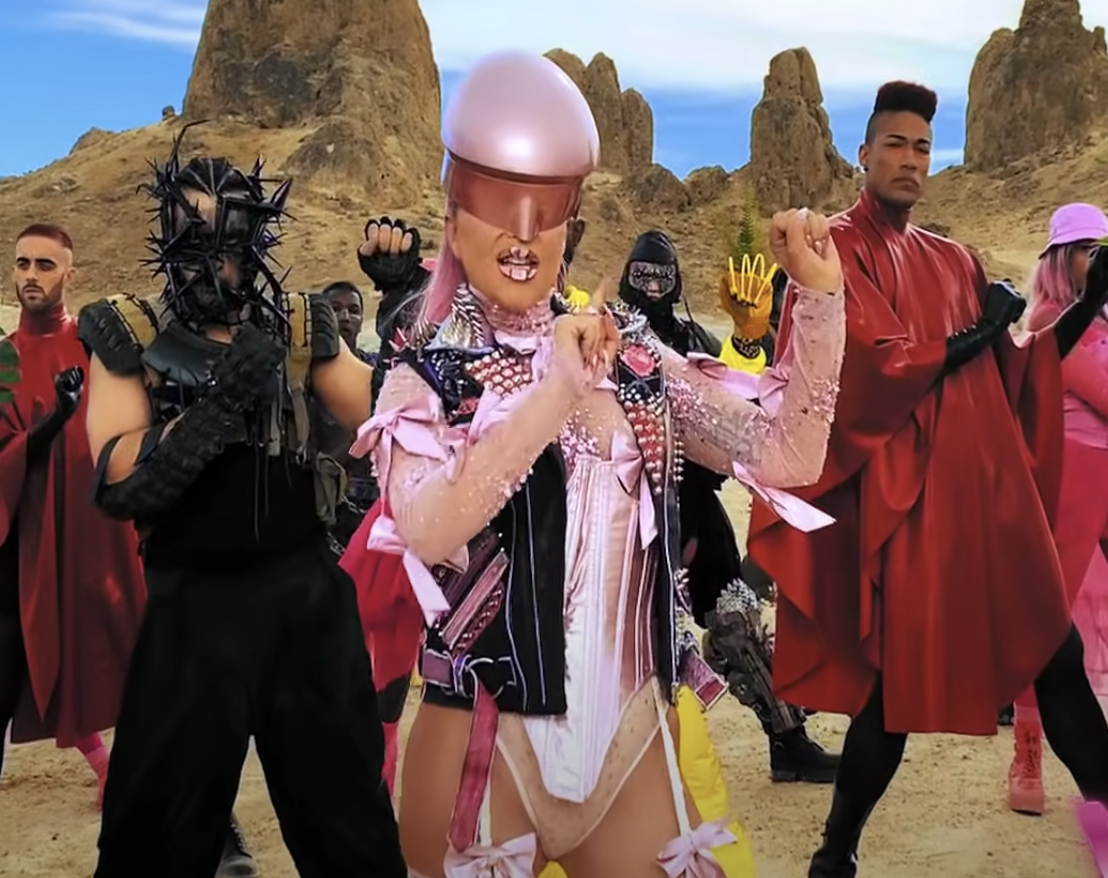Gaga wearing a large helmet headpiece while dancing
