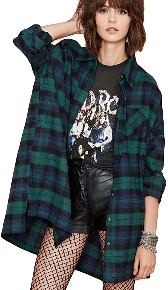 Model wearing oversized shirt with blue, green, and dark blue flannel