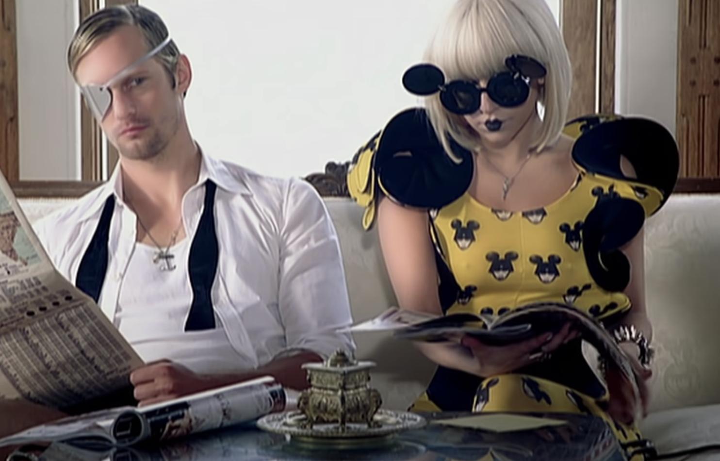 Gaga sitting alongside Alexander Skarsgard as she flips through a magazine