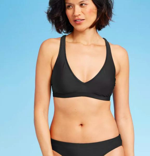 Model wears black bralette bikini top with matching bottoms