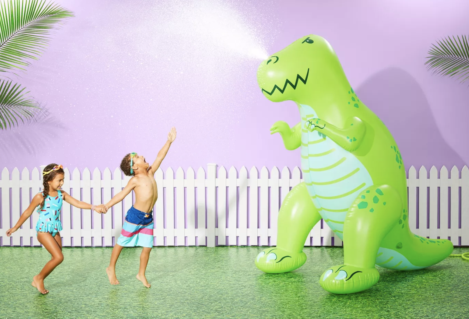Two kids in swimsuits playing next to the six foot inflatable dinosaur that shoots out water from its nose