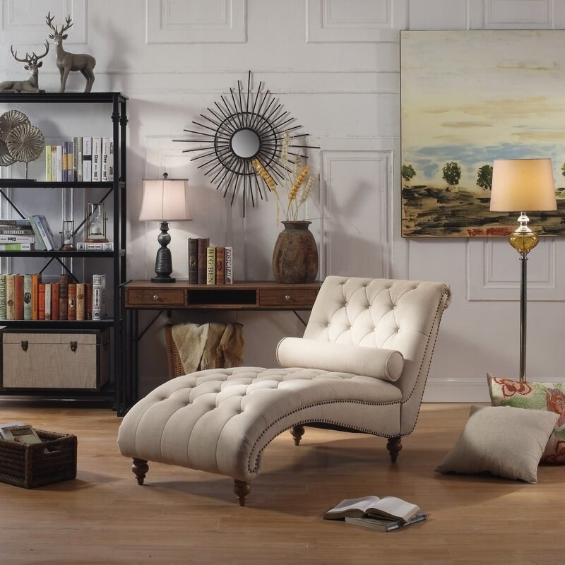 The chaise in beige with no a curved, tufted design and wooden feet